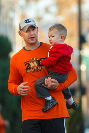 BOISE, IDAHO - NOVEMBER 22:  Man holds his son while competing in The 5k Turkey Day race in Boise, Idaho on November 22, 2012