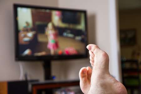 family sofa: Shallow depth of field with feet in focus of a guy watching family movies on the TV in the background Stock Photo