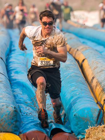 mud slide: BOISE, IDAHOUSA - AUGUST 10: Person 8385 runs down the slide full speed at the The Dirty Dash in Boise, Idaho on August 10, 2013