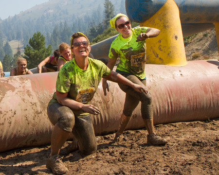 BOISE, IDAHOUSA - AUGUST 10: Two women as they finish one of the obstacles at the The Dirty Dash in Boise, Idaho on August 10, 2013