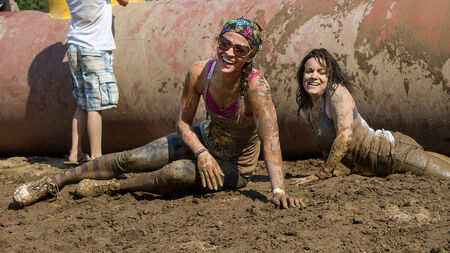 BOISE, IDAHOUSA - AUGUST 10: Two unidentified runners on the ground smiling after falling off an obstacle at the The Dirty Dash in Boise, Idaho on August 10, 2013