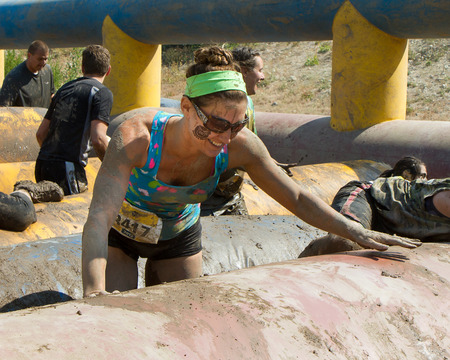 BOISE, IDAHOUSA - AUGUST 10: Runner 3417 smiles as she climbs over an obstacle at the The Dirty Dash in Boise, Idaho on August 10, 2013 Editorial