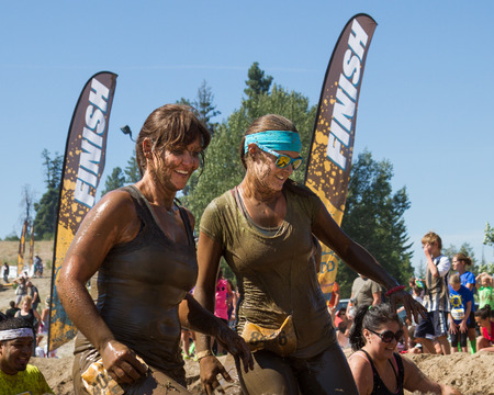 BOISE, IDAHOUSA - AUGUST 10: Runners smile as they complete the 10k Dirty Dash in Boise, Idaho on August 10, 2013