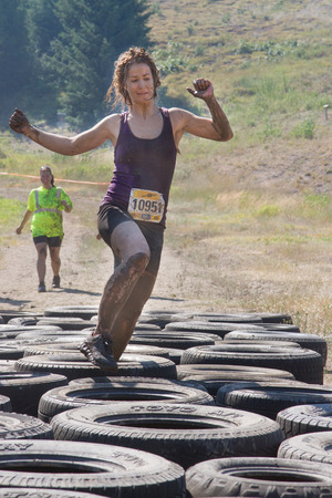 BOISE, IDAHOUSA - AUGUST 10: Runner 10951 steps over the tires during one of the obstacles at the The Dirty Dash in Boise, Idaho on August 10, 2013