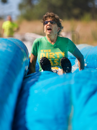 mud slide: BOISE, IDAHOUSA - AUGUST 10, 2013:  Runner 9230 makes a funny expression while going down the slide at the The Dirty Dash Editorial