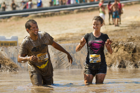 BOISE, IDAHO/USA - AUGUST 10, 2013: Runner 9738 and 9737 have fun at  at the mud pit during The Dirty Dash