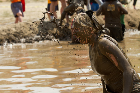 contestant: BOISE, IDAHOUSA - AUGUST 11, 2013: Unidentified woman gets a splash of mud thrown her way at the dirty dash Editorial