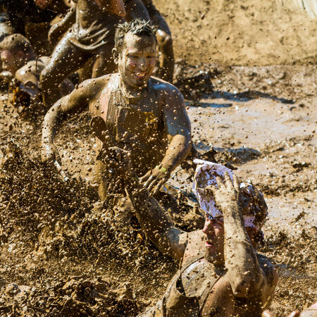 BOISE, IDAHOUSA - AUGUST 25 - Group of people play in the mud making a big splash  The Dirty dash is a 10k run through obstacles and mud on August 25, 2012 in Boise, Idaho