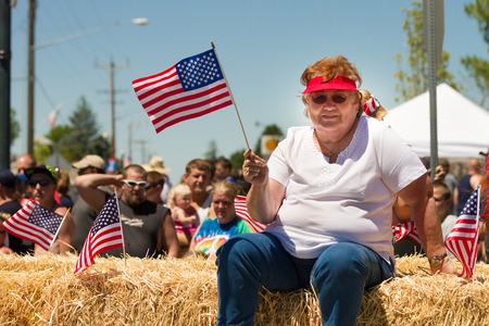 MIDDLETON, IDAHO - JULY 4: Lavena Gardner waving an american flag during the fourth of july parade of 2012 in Middleton, Idaho