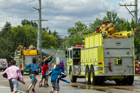 watergun: EAGLEIDAHO - JUNE 9: Children are trying to squirt firemen sitting on top of their firetrucks during the Eagle Fun Days in Eagle, Idaho on June 9th, 2012 Editorial