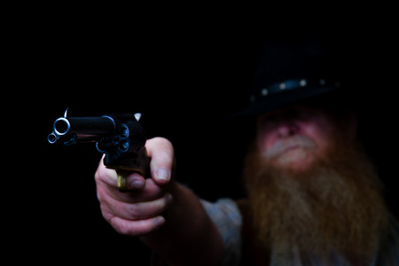 Image shows an older cowboy holding his pistol up in the middle of the night hiding about ready to shoot