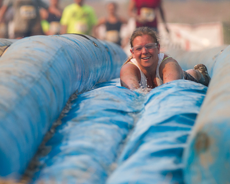 mud slide: BOISE, IDAHOUSA - AUGUST: Unidentified woman slides face first down the slide at the The Dirty Dash in Boise, Idaho on August , 2013