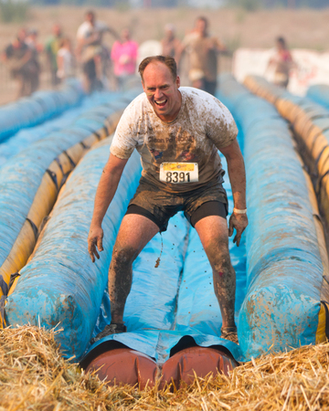 mud slide: BOISE, IDAHOUSA - AUGUST 10:Unidentified man stands at the end of the slide during the The Dirty Dash in Boise, Idaho on August 10, 2013