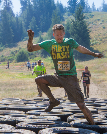 BOISE, IDAHOUSA - AUGUST 10: A runner with bib number 9736 does tries his luck through the tire obstacles at the The Dirty Dash in Boise, Idaho on August 10, 2013