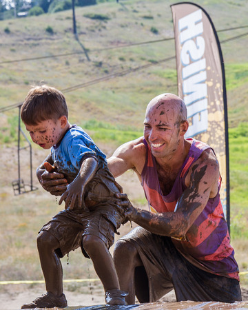 BOISE, IDAHOUSA - AUGUST 11: Unidentified man helps a child up near the finish line of the The Dirty Dash in Boise, Idaho on August 11, 2013