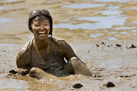 mud pit: BOISE, IDAHOUSA - AUGUST 11:Unidentified woman stuck in the pit sitting on her bum at the The Dirty Dash in Boise, Idaho on August 11, 2013
