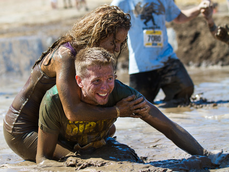 mud pit: BOISE, IDAHOUSA - AUGUST 10: Unidentified couple horsing around in the mud pit near the finish at the The Dirty Dash in Boise, Idaho on August 10, 2013