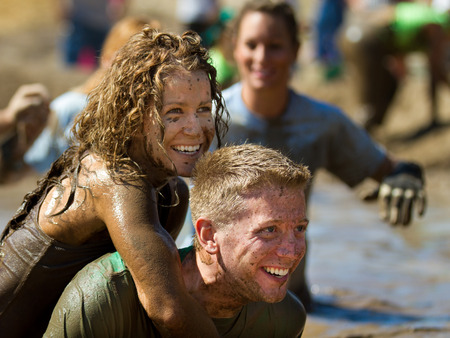 mud pit: BOISE, IDAHOUSA - AUGUST 10: Unidentified couple smiling after finishing the The Dirty Dash in Boise, Idaho on August 10, 2013  Editorial
