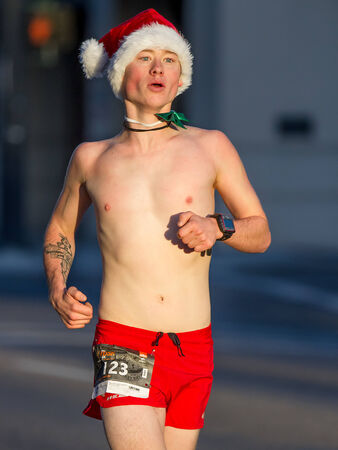 BOISE, IDAHO - NOVEMBER 22: Man running topless in the cold morning wearing a Santa Hat during The Turkey Day 5kin Boise, Idaho on November 22, 2012