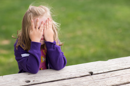 Preschooler playing game of hide and sick. Right now she is sitting on the table covering her eyes while taking a sneaky peek. Stock Photo