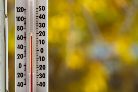 Thermometer against fall foilage that is heavily out of focus Stock Photo