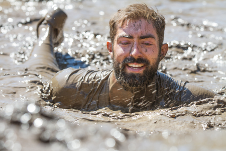 mud pit: BOISE, IDAHOUSA - AUGUST 10: Unidentified man smiles while swiming through the mud at the The Dirty Dash in Boise, Idaho on August 10, 2013