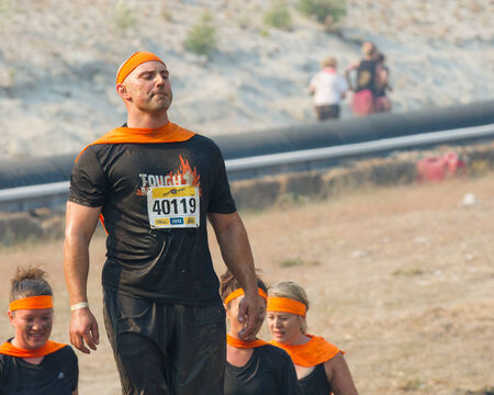 BOISE, IDAHOUSA - AUGUST 10: MAn 40119 stands with his superhero cape at the The Dirty Dash in Boise, Idaho on August 10, 2013