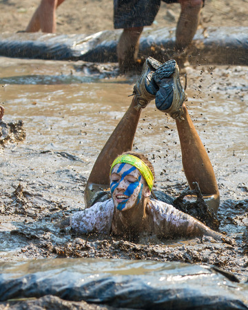 BOISE, IDAHOUSA - AUGUST 10: Unidentified woman fell into the mud pit at the The Dirty Dash in Boise, Idaho on August 10, 2013