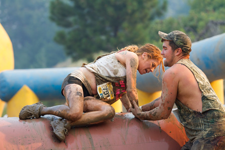 BOISE, IDAHOUSA - AUGUST 10: Unidentified runner being helped over an obstacle at the The Dirty Dash in Boise, Idaho on August 10, 2013 Editorial