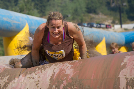 BOISE, IDAHOUSA - AUGUST 10: Runner 40469 smlies while she attempts the hurdle at the The Dirty Dash in Boise, Idaho on August 10, 2013