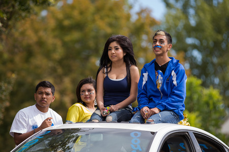 CALDWELL, IDAHOUSA - SEPTEMBER 27:Four unidentified students sitting on the top of a car at the Caldwell High School Homecoming parade on September 27, 2013  Editorial