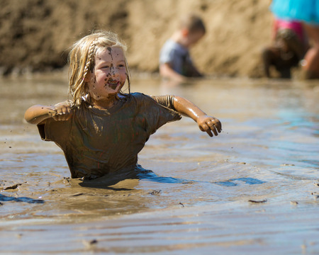 BOISE, IDAHOUSA - AUGUST 10: Child works their way through the pit of mud at the The Dirty Dash in Boise, Idaho on August 10, 2013
