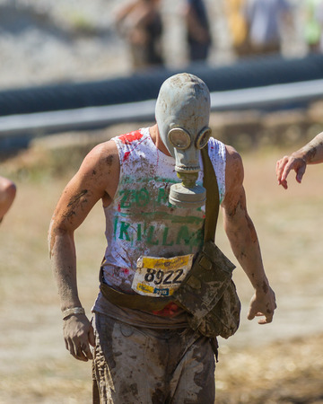BOISE, IDAHOUSA - AUGUST 10: Runner 8922 observes the course at the The Dirty Dash in Boise, Idaho on August 10, 2013 while he wears a gas mask Editorial