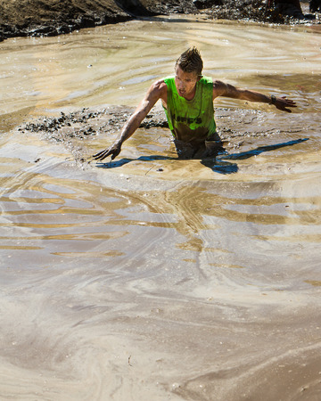 BOISE, IDAHOUSA - AUGUST 10: Unidentified person making a struggle to get through the thick mud at the The Dirty Dash in Boise, Idaho on August 10, 2013