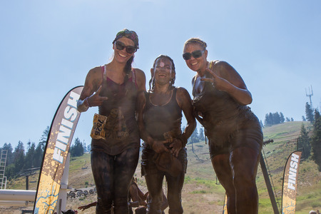 BOISE, IDAHOUSA - AUGUST 10: Three runners at the finish line posing for the camera at the The Dirty Dash in Boise, Idaho on August 10, 2013
