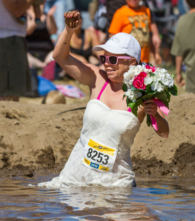 wet dress: BOISE, IDAHOUSA - AUGUST 10, 2013: Runner 8253 ruins her wedding dress walking through the mud at at the The Dirty Dash