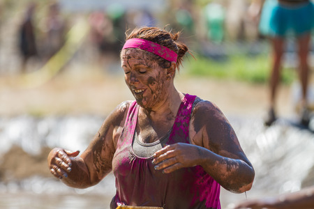 mud woman: BOISE, IDAHOUSA - AUGUST 10, 2013: Unidentified woman covered in mud near the end of the race at the The Dirty Dash