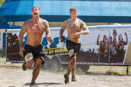 BOISE, IDAHOUSA - AUGUST 10, 2013: Two men run fast to finish the race at the The Dirty Dash