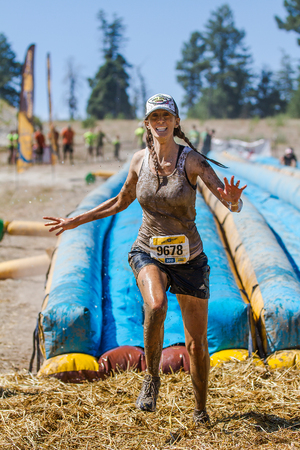 mud pit: BOISE, IDAHOUSA - AUGUST 10, 2013: Runner 9678 just passed the slide and now runs to the mud pit at the The Dirty Dash