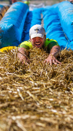 BOISE, IDAHOUSA - AUGUST 10, 2013: Face first, an unidentified runner slides into the hay at the The Dirty Dash Editorial