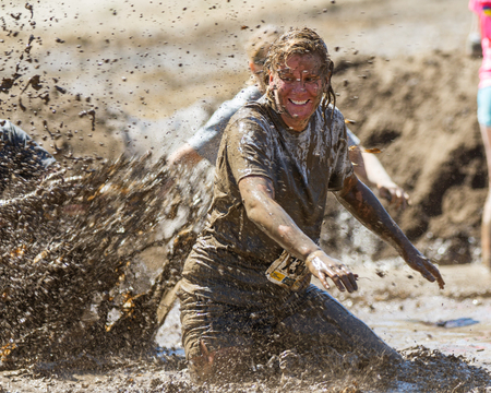 BOISE, IDAHOUSA - AUGUST 10, 2013: Runner 7358 tries to get away from someone making a big splash at the The Dirty Dash