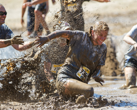 BOISE, IDAHO/USA - AUGUST 10, 2013: Runner 7358 smiles as she is getting splashed at the The Dirty Dash