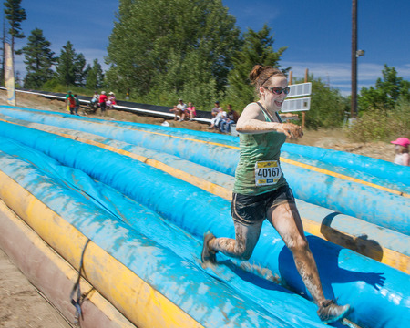 mud slide: BOISE, IDAHOUSA - AUGUST 10, 2013: Runner 40167 sprints down the sldie at the The Dirty Dash