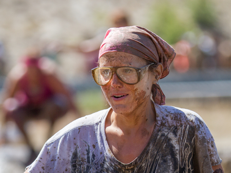 BOISE, IDAHOUSA - AUGUST 10, 2013: Unidientifed woman with glasses pauses for a moment at the The Dirty Dash Editorial