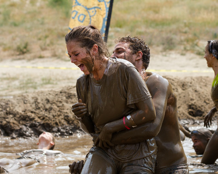 BOISE, IDAHOUSA - AUGUST 11, 2013: Woman tries to relax in the mud near the end of the race at the dirty dash Editorial