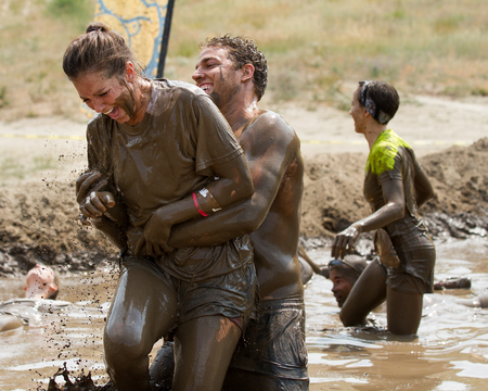 BOISE, IDAHOUSA - AUGUST 11, 2013: Unidentified man picks up a woman during the race at the dirty dash