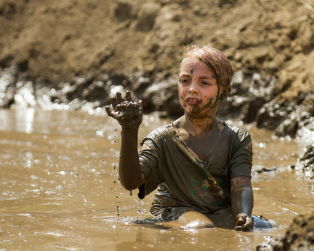 BOISE, IDAHOUSA - AUGUST 11, 2013: Unidentified child plays with the mud at the dirty dash 新聞圖片