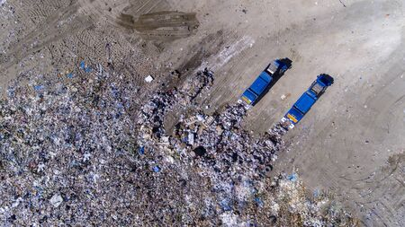 dumping of trash in a landfill by two trucks
