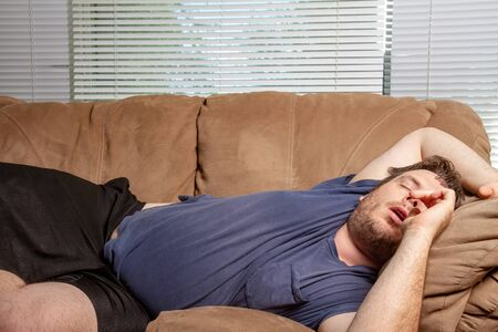 fat tired man passed out on the couch Stockfoto - 132021451