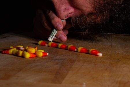 Bearded man trying to snort up the treat candy corn during fall right before halloween